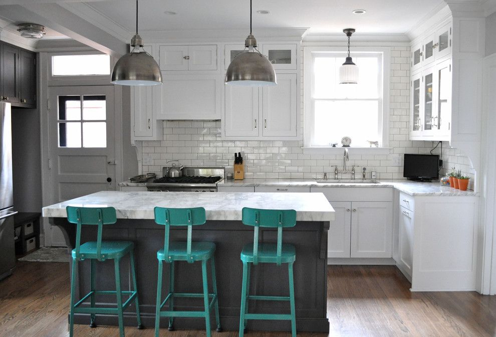 White marble counter top with green chairs and subway tiles