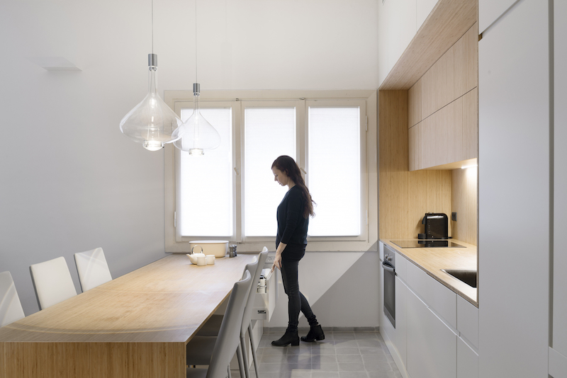 The kitchen area integrates the dining space as well, featuring a minimalist and generously-sized table