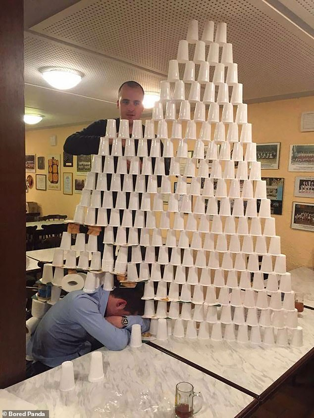 One man decided to build a pyramid on top of his seemingly unaware sleeping friend at a bar