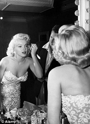 Showgirl: Marilyn Monroe applying make up at her mirror