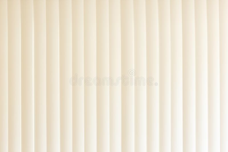 Abstract louver vertical blinds background in tan. Abstract creative textured louver vertical blinds background in tan colors with dramatic side lighting stock photos