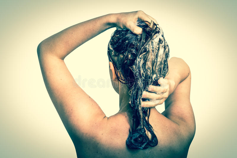 Attractive woman washing hair with shampoo in shower. On white background - retro style stock photo