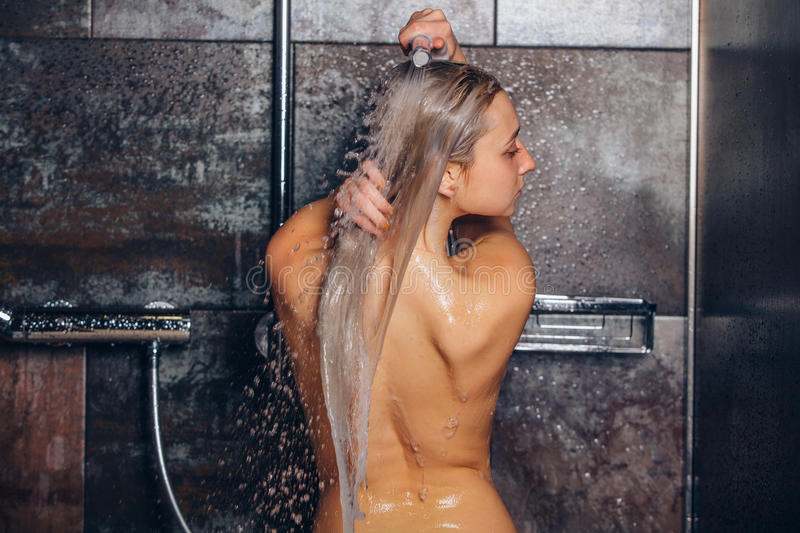 Autiful woman standing at the shower. is washing her hair. Autiful woman standing at the shower. Woman is washing her hair royalty free stock photography