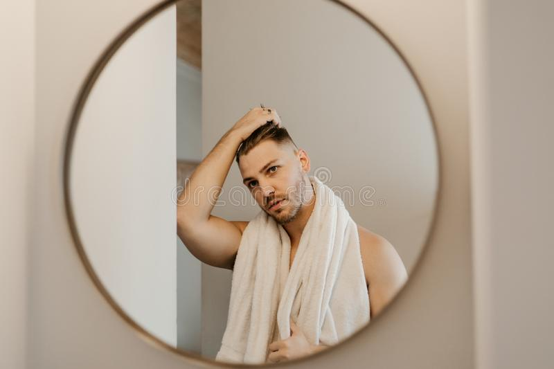Young Attractive Male Model Washing Hair in Trendy Modern Subway Tile Wet Shower. Bathroom Shower Scene washing Hair with shampoo in modern remodeled shower stock photos