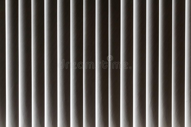Beautiful horizontal texture of vertical fabric beige blinds shuts the sunlight from the window. A beautiful horizontal texture of vertical fabric beige blinds stock photography