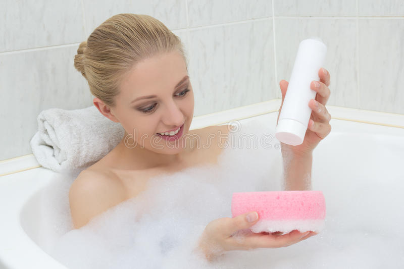 Beautiful woman washing in bath with sponge and shower gel. Young beautiful woman washing in bath with sponge and shower gel stock images
