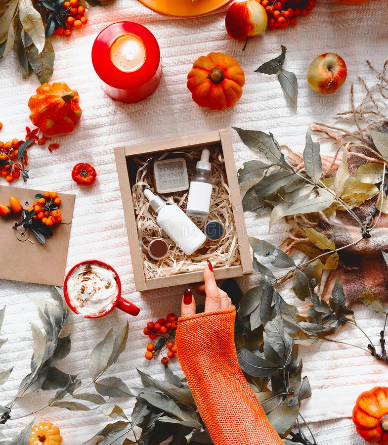 Beauty and autumn skin care concept. Female hand in orange knitted sweater opens beauty box with cosmetic products on desktop with royalty free stock photo