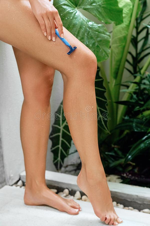 Beauty woman legs. Young woman shaving her legs in the bath. Wet feet, women legs in the shower. Girl washing her legs. Closeup ph. Beauty woman legs. Young stock photos