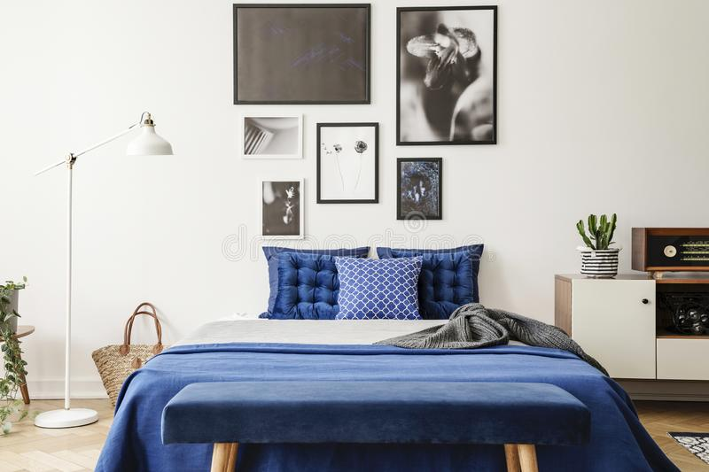 Bench in front of bed with navy blue pillows between lamp and cabinet in bedroom interior. Real photo. Concept royalty free stock photos