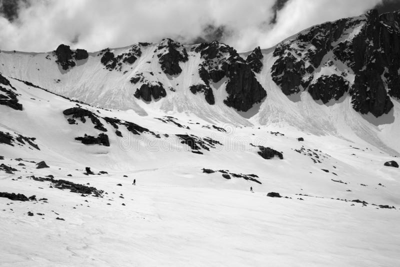 Black and white high mountains with snow cornice and avalanche trail. High mountains with snow cornice and avalanche trail, snowy plateau and two small stock photo
