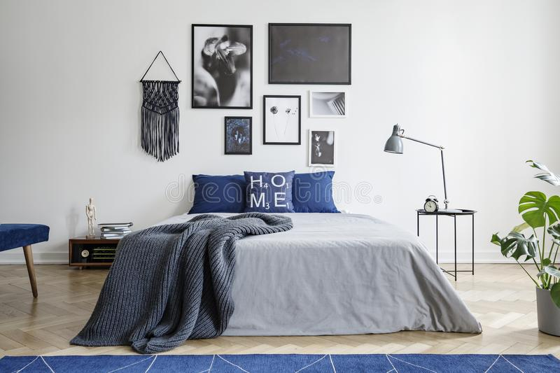 Blanket on bed with blue pillows in white bedroom interior with gallery and lamp on table. Real photo. Concept stock photo