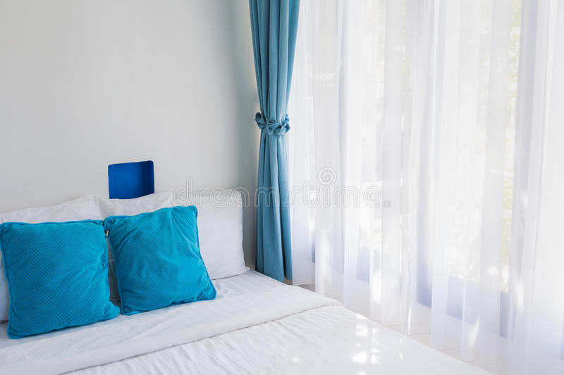 Blue theme pillows white bedroom light curtain. Light blue theme pillows white mattress bedroom light through curtain royalty free stock image