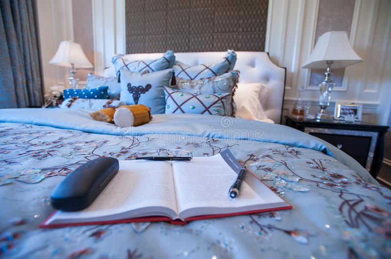 A book in a Blue Bedroom in a mansion. Blue Bedroom in a mansion,blue silk Quilt.Soft pillow.White lamps.Wood decoration.A book laid on the bed stock image
