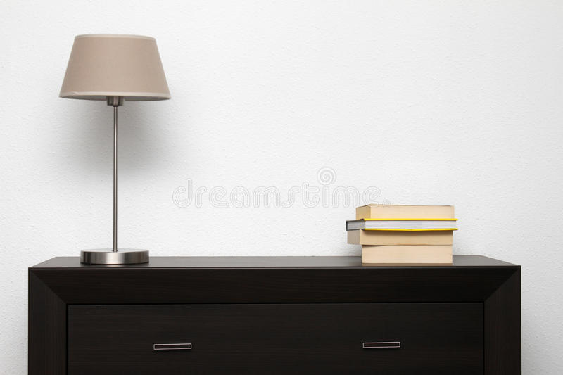 Brown commode with lamp and books in minimalism interior. Brown commode with lamp and books in bright minimalism interior stock images