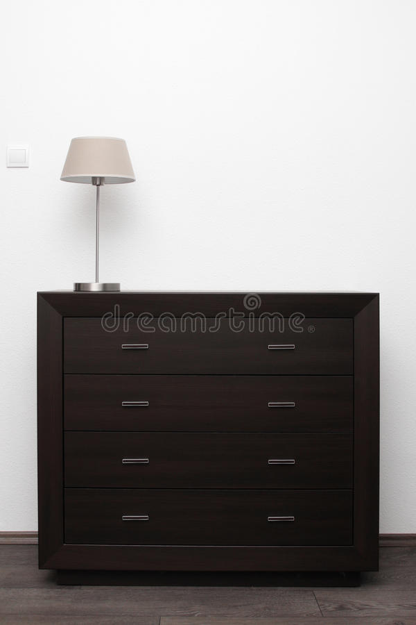 Brown commode with lamp in minimalism interior. Brown commode with lamp in bright minimalism interior royalty free stock images