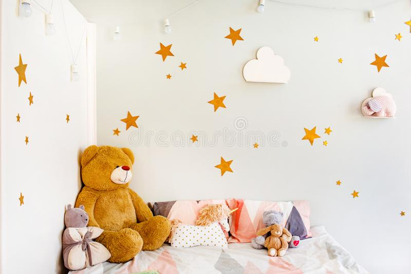 Child dream concept. Cosy bedroom decorated with toys and stars. Stars and white clouds on walls royalty free stock photo