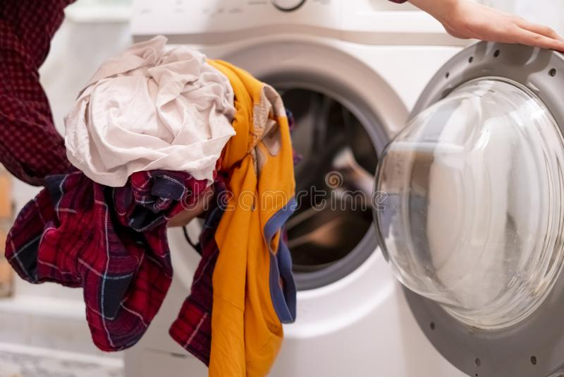 close up hands loading dirty clothes into washing machine at home bathroom f royalty free stock photos