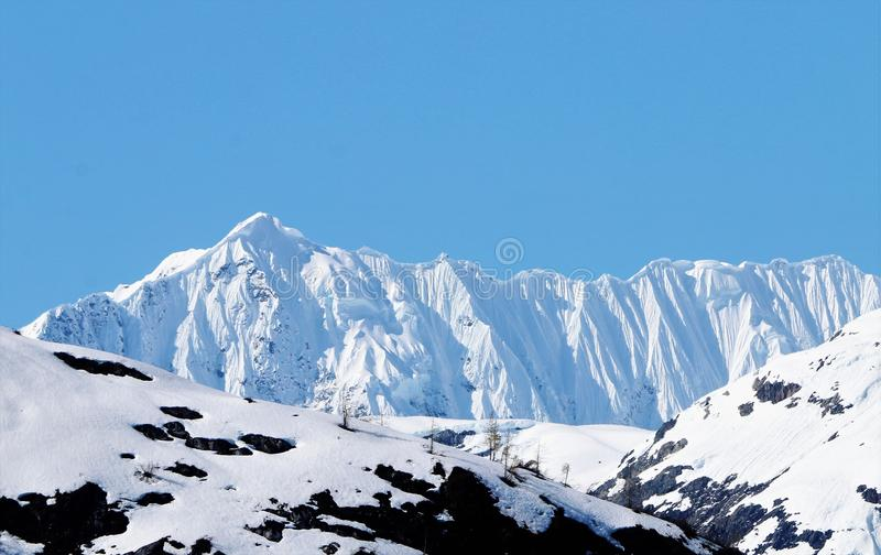 Cornice on snow capped ridge in Alaska. High wall or cornice of snow on a ridge line of mountains in Alaska royalty free stock photo