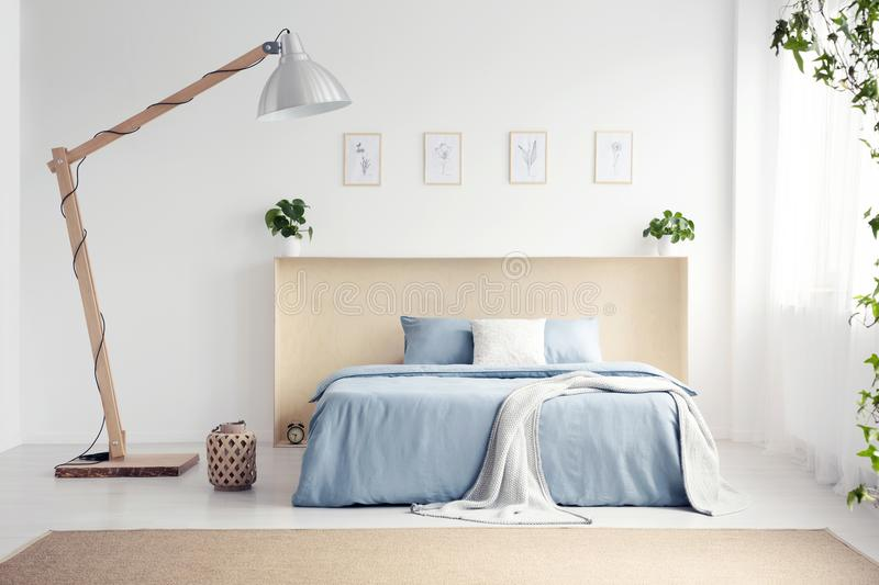 Designer lamp next to blue bed with blanket in white bedroom int. Erior with posters. Real photo royalty free stock image