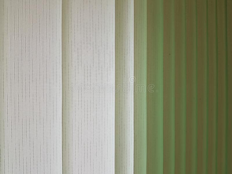 Fabric blinds in the form of green vertical stripes. royalty free stock photography