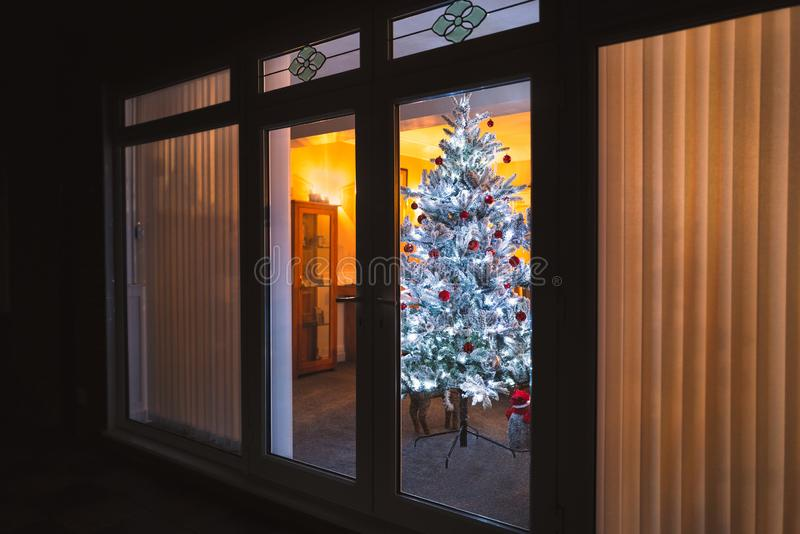 A frosted white artificial christmas tree with red and silver decorations seen through large patio doors with vertical slat blinds. And bevel window designs stock photos