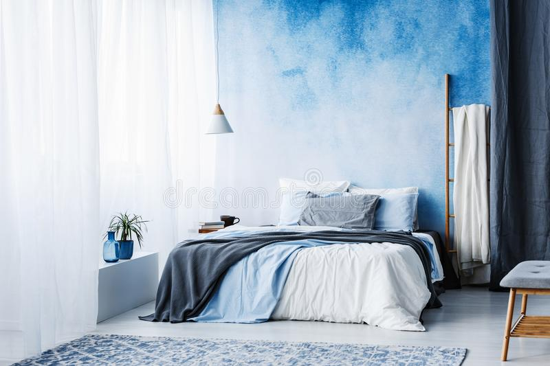 Grey and blue bedding on bed against ombre wall in minimal bedroom interior with ladder royalty free stock photos