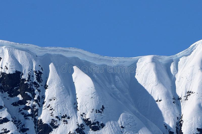 Closeup of a cornice on snow capped ridge in Alaska. High wall or cornice of snow on a ridge line of mountains in Alaska. Height estimate at least 20 feet or royalty free stock photography