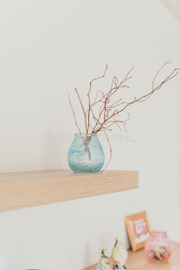Light shelf on the wall with decor. Scandinavian minimalism in the interior. Light shelf on the wall with decor. A branch in a vase. Scandinavian minimalism in stock photos