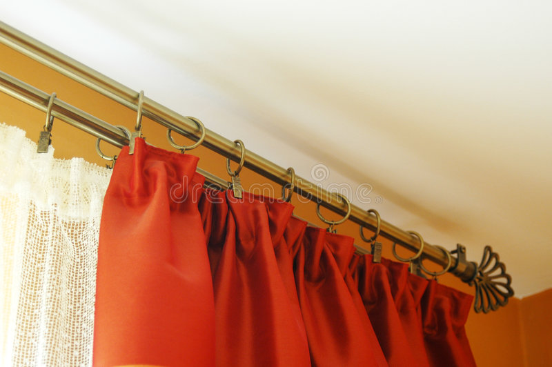 Living room window treatment. A view of curtain rods and red curtains or drapes hung as window treatment for a living room window royalty free stock image