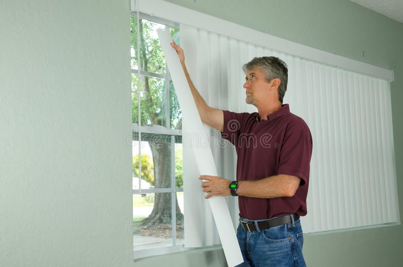 Man hanging vertical blinds home repair maintenance. A handy man home repair service technician or home owner hanging white vertical blinds for the window royalty free stock photography