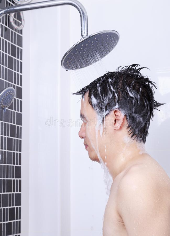 Man are taking a rain shower and washing hair in bathroom. Man are taking a rain shower and washing hair in the bathroom royalty free stock image