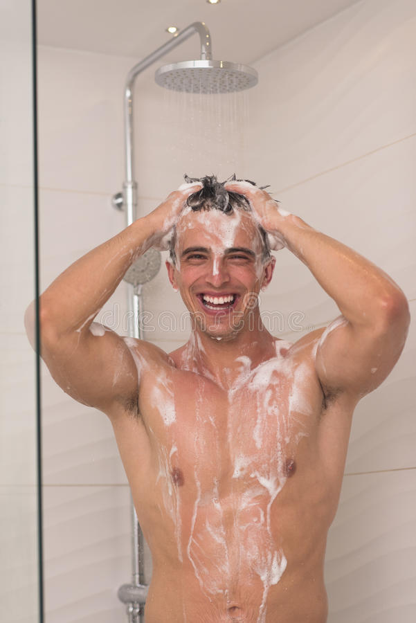 Man taking shower in bath. Young good looking and attractive man with muscular body wet taking shower in bath stock image