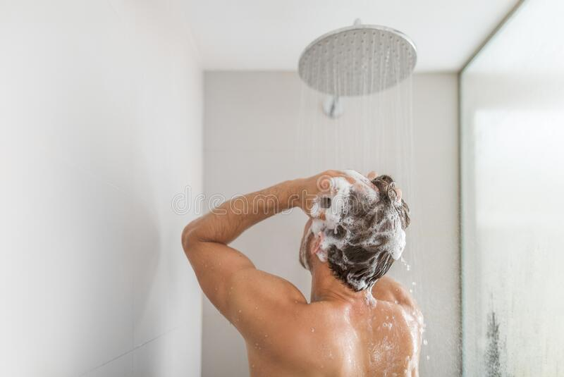 Man taking a shower washing hair under water falling from rain showerhead in luxury walk-in bath. Showering young person. At home lifestyle. Body care morning royalty free stock images