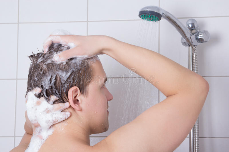 Man washing his hair in shower. Young man washing his hair in shower stock photos
