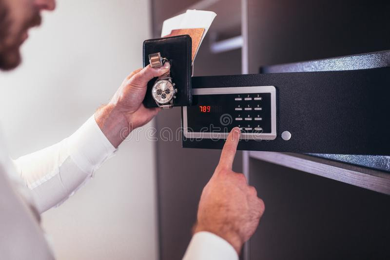 Men`s hand opens a safe hidden in the wardrobe. stock photography