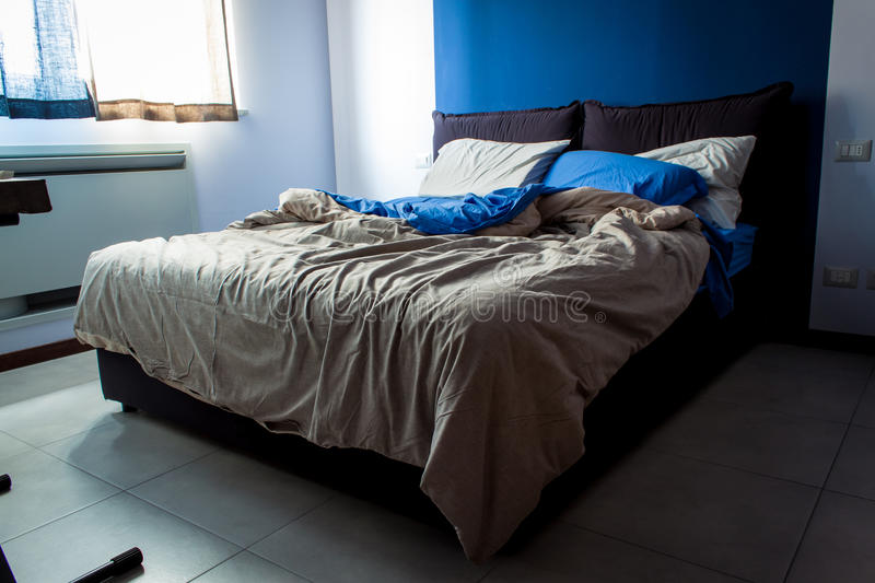Messy bedroom sheets. A little bedroom, light bedsheets, the main color is blue stock photos