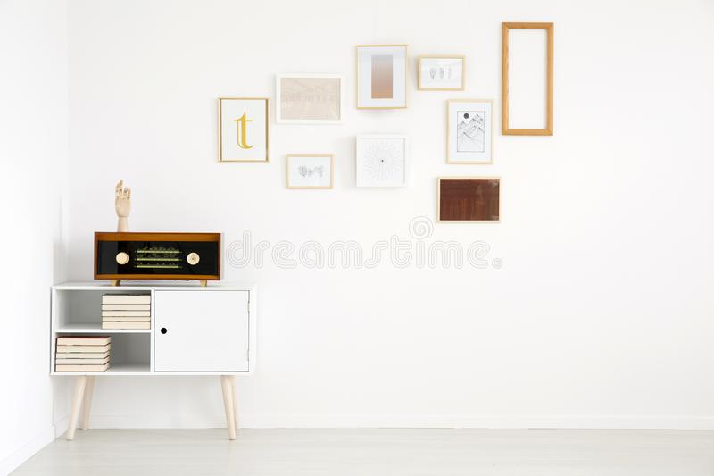 Minimalism in living room interior. With pictures gallery on white, empty wall and vintage radio on cupboard stock images