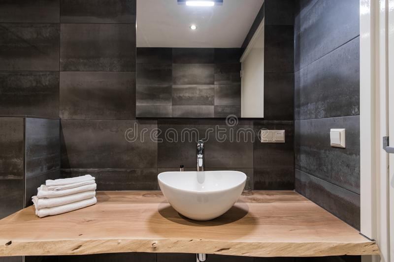 Modern interior of the bathroom. The washbasin is made of white massive shell on the table of wood. Minimalism and. Simplicity in a bright grey functional stock images