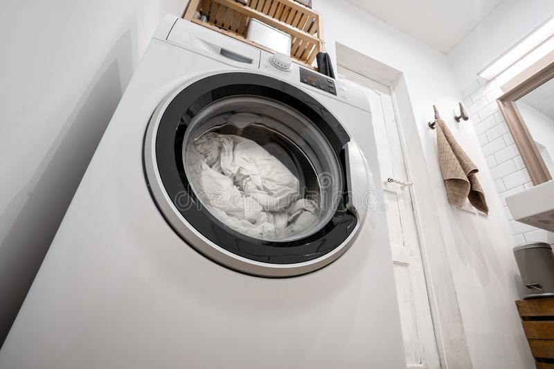 New washing machine with bedding inside, in the interior of a bright bathroom with shelves royalty free stock photography