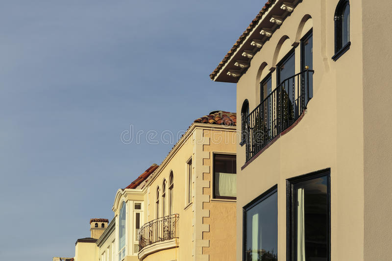 A row of upscale houses with roof and cornice detail. A row of beige and peach houses with roof, balcony, and cornice detail. The houses sit against a blue sky stock photography