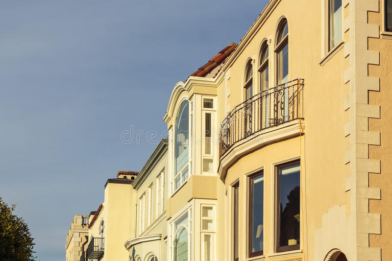 A row of upscale houses with roof and cornice detail. A row of beige and peach houses with roof, balcony, and cornice detail. The houses sit against a blue sky stock photo