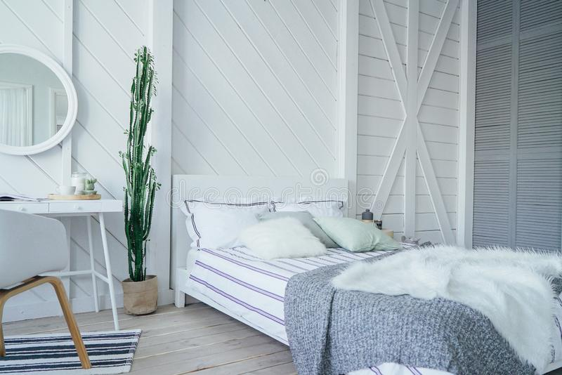 Scandinavian modern cozy eco interior, white table and mirror in bed room, minimalism. The Scandinavian modern cozy eco interior, white table and mirror in bed royalty free stock photo