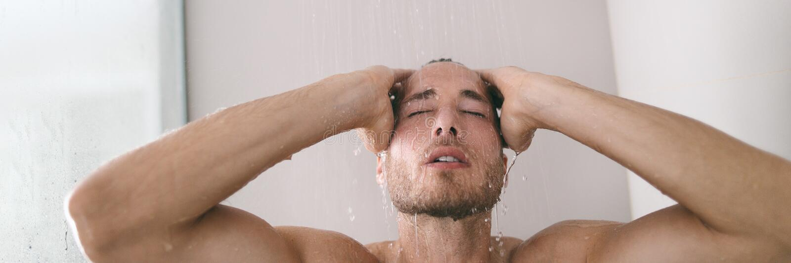 Shower bathroom in luxury hotel or home man taking hot bath washing hair under rainfall water banner panorama.  royalty free stock photography