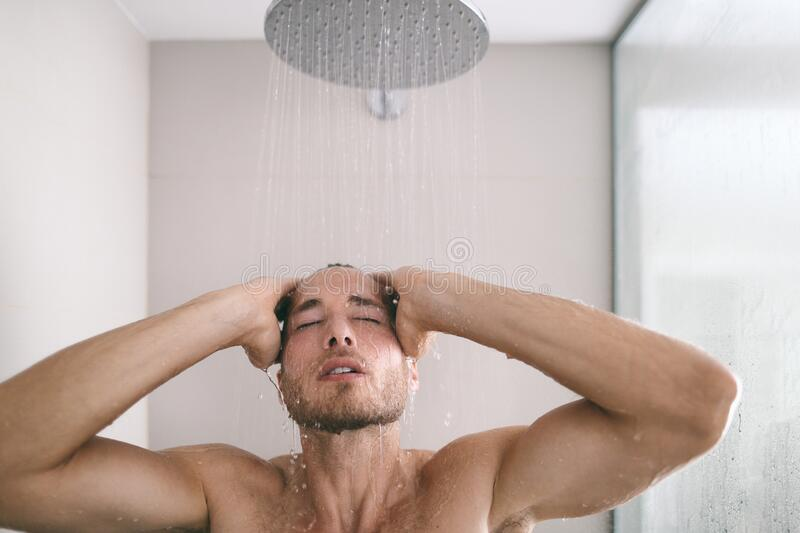 Shower man taking hot bath washing hair and body in hotel luxury bathroom. Relaxing skincare men beauty. Shower man taking hot bath washing hair and body in stock photography