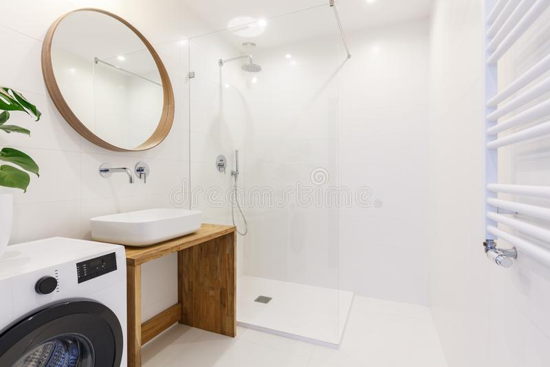 Side view of a modern bathroom interior with a shower, wash basin, round mirror, washing machine and wall radiator royalty free stock photography