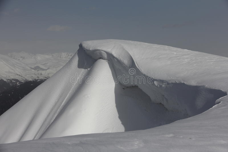 Snow cornice in mountains of Caucasus, Russia. Avalanche danger stock photography