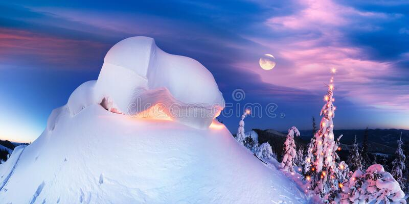 Snowy cornice on the mountain at night. Snow cornice at the top is a snow formation formed in the mountains under the influence of wind. Artistic illumination royalty free stock image