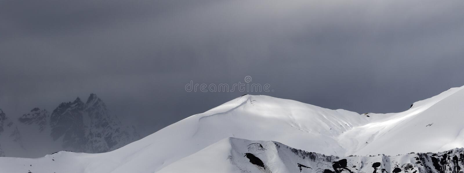 Sunlight mountains with snow cornice and trace from avalanche before blizzard. Panoramic view on sunlight mountains with snow cornice and trace from avalanche royalty free stock photography