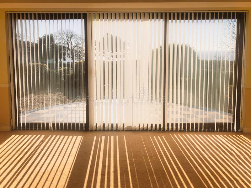 Sunlight shining through full length white vertical blinds in front of three glass sliding french doors leading to a patio. Sunlight shining through full length stock photos