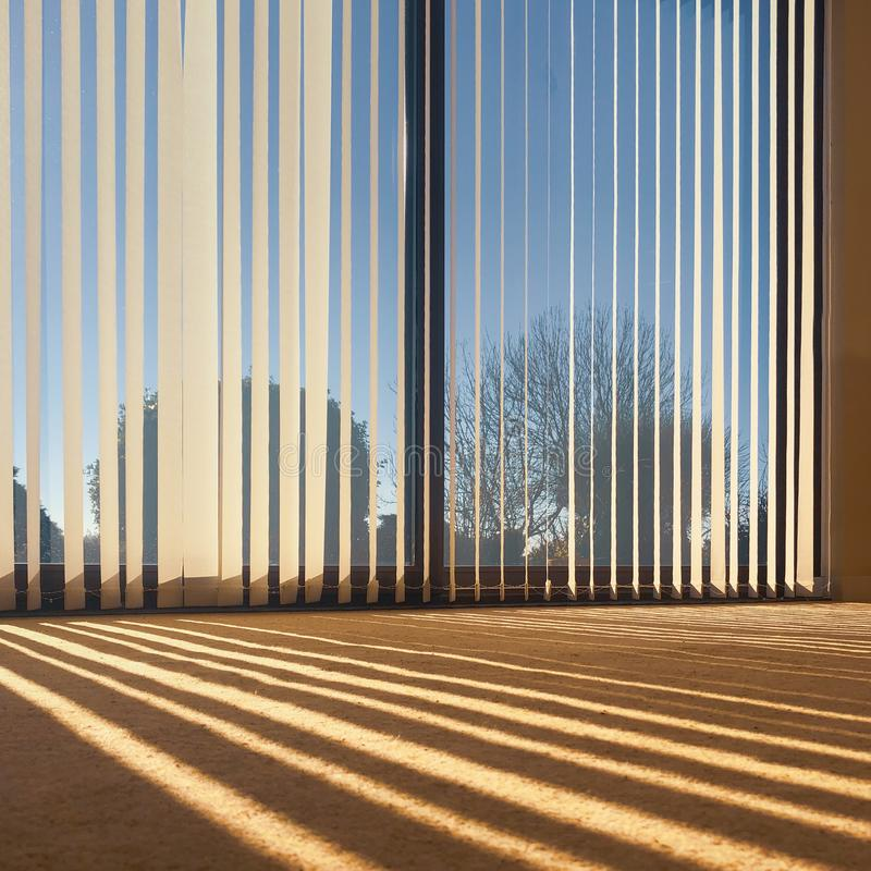 Sunlight through vertical blinds angled slightly open hanging over large sliding interior glass doors. And throwing a striped shadow on to a beige carpet stock images